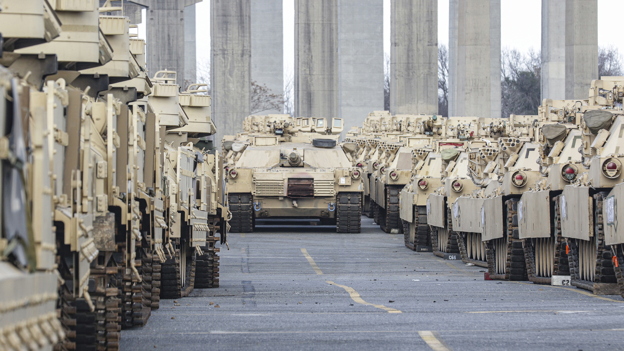 An M1A1 Abrams Tank sits in the distance among various armored track vehicles in Savannah, GA, on Feb. 5, 2020. This equipment was staged in preparation for the DEFENDER-Europe 20 exercise which takes place in multiple European countries. Strategic readiness includes the ability of the U.S. military to dynamically project force and set the theater by mobilizing and deploying forces, sustaining them in a crisis, and redeploying them when their mission is complete. (U.S. Army Photo by Pfc. Daniel Alkana/ 22nd Mobile Public Affairs Detachment)