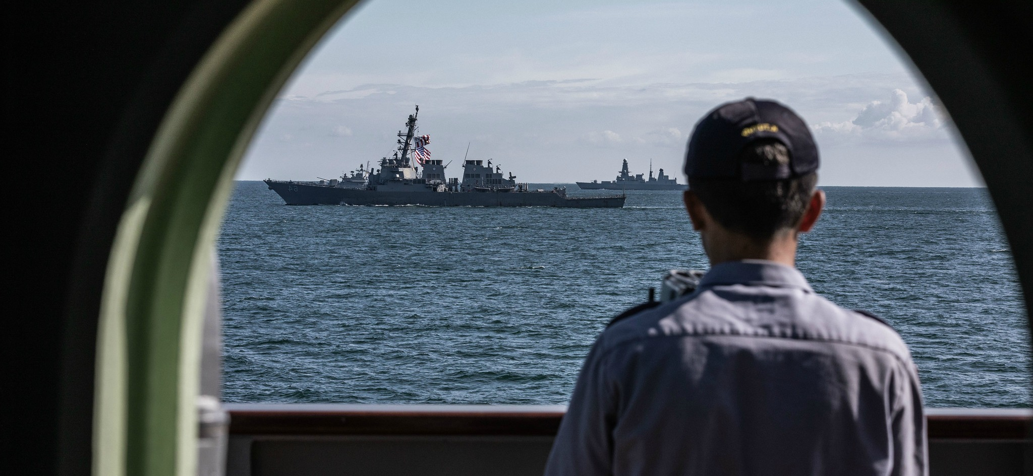 A Turkish sailor watches a formation of warships from the frigate TCG Turgutreis during Exercise Sea Breeze 2019, a multinational maritime exercise co-led by the United States and Ukraine. Nineteen nations participated, including 15 NATO Allies.