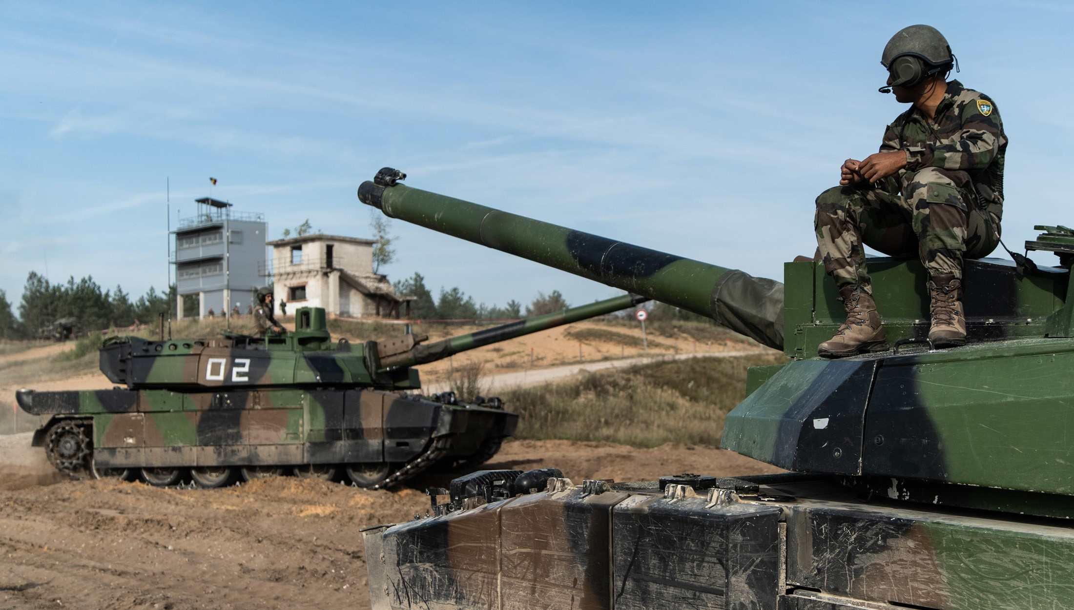 A French Army tank crewman watches a Leclerc battle tank move through the staging area in Ādaži, Latvia during Exercise Furious Hawk. The French tanks are deployed to NATO's enhanced Forward Presence Battlegroup in Estonia.
