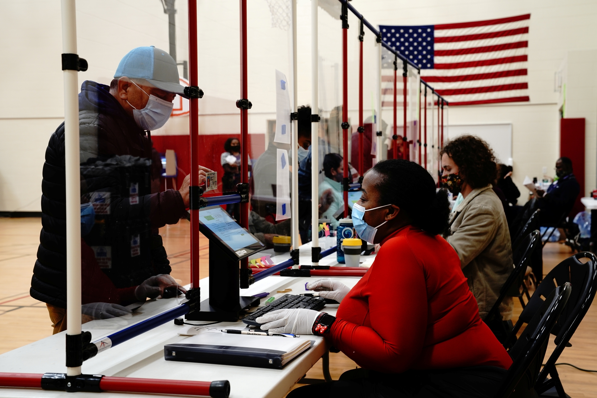 Photo: Poll worker Kim Stafford helps a voter on Election Day at a polling station inside Knapp Elementary School in Racine, Racine County, Wisconsin, U.S., November 3, 2020. Credit: REUTERS/Bing Guan