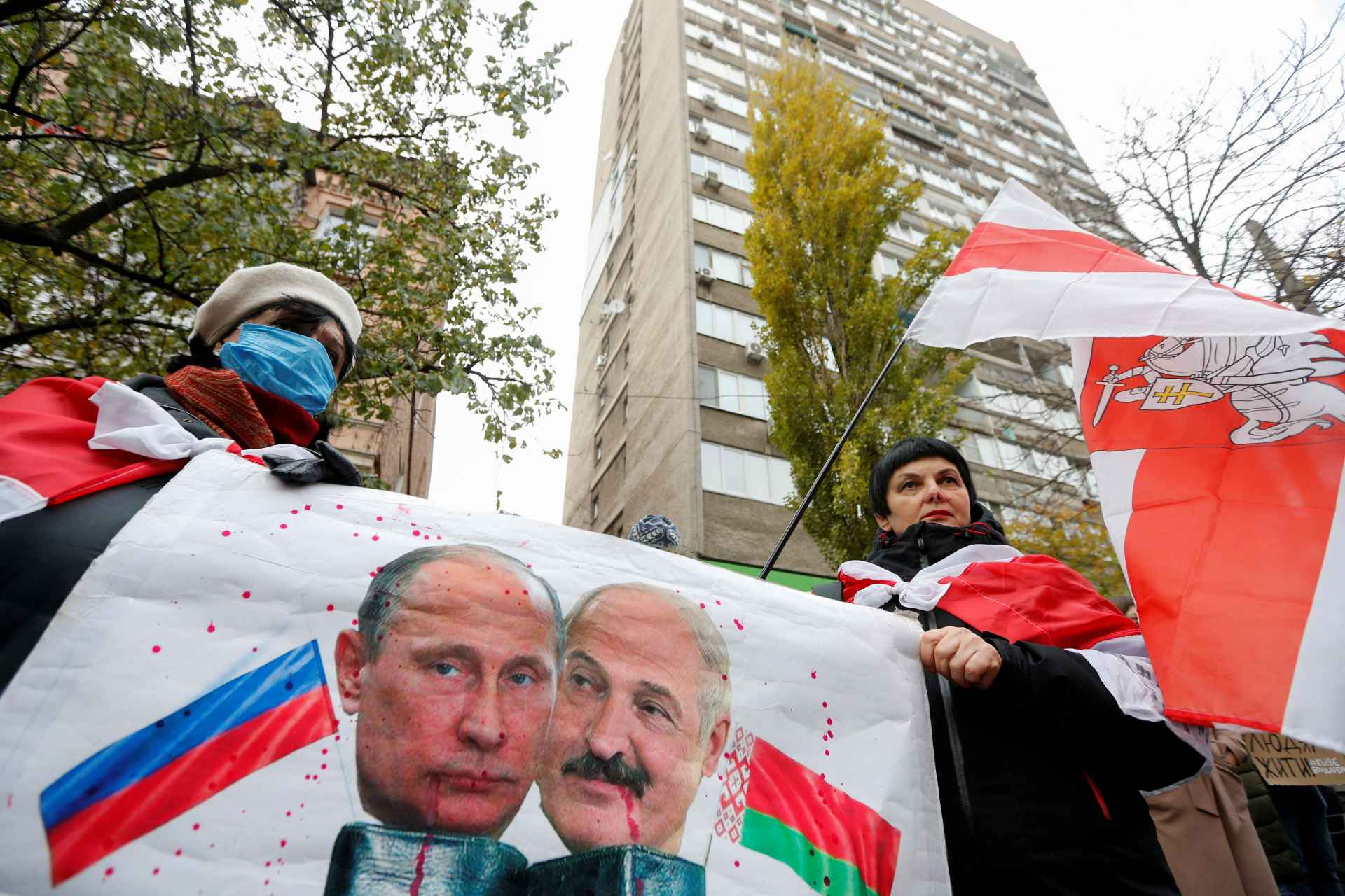 Photo: People gather to mourn the death of Belarusian anti-government protester Roman Bondarenko, who was allegedly beaten by the country's security forces in Minsk, outside the Belarusian embassy in Kyiv, Ukraine November 13, 2020. A placard displays images depicting Russian President Vladimir Putin and Belarusian President Alexander Lukashenko. Credit: REUTERS/Valentyn Ogirenko