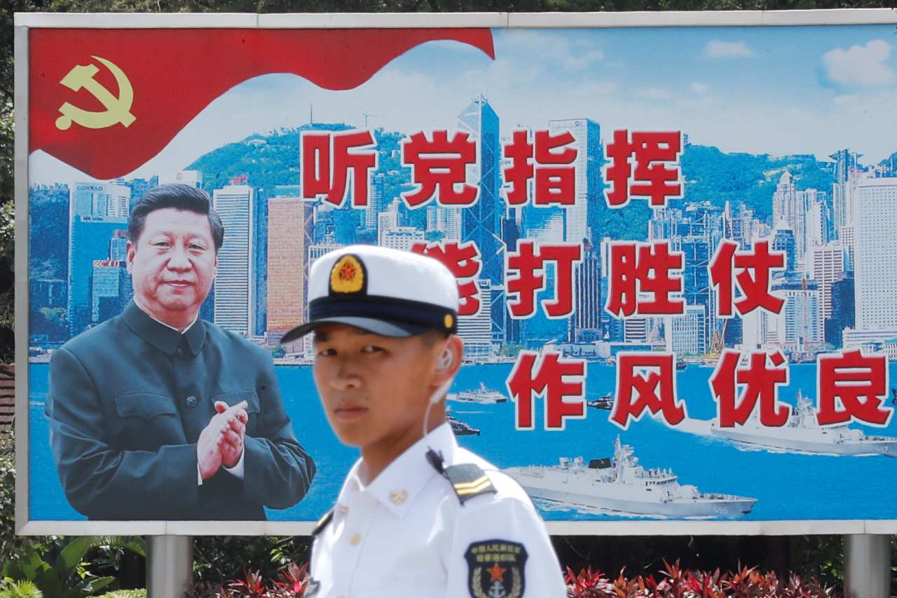Photo: A People's Liberation Army Navy soldier stands in front of a backdrop featuring Chinese President Xi Jinping during an open day of Stonecutters Island naval base, in Hong Kong, China, June 30, 2019. Credit: REUTERS/Tyrone Siu