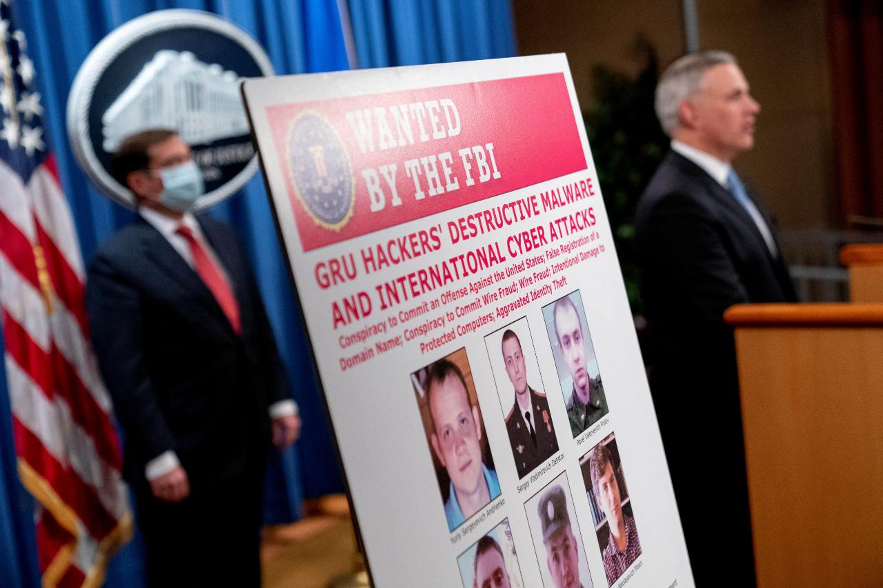 Photo: A poster showing six wanted Russian military intelligence officers is displayed as U.S. Attorney for the Western District of Pennsylvania Scott Brady, accompanied by Assistant Attorney General for the National Security Division John Demers, speaks at a news conference at the Department of Justice, in Washington, U.S., October 19, 2020. Credit: Andrew Harnik/Pool via REUTERS