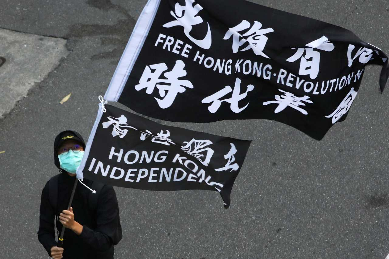 "Photo: A protester holds a ""Free Hong Kong revolution"" flag during a rally calling China to release 12 Hong Kong people arrested at sea by mainland authorities, in Taipei, Taiwan, October 25, 2020. Credit: REUTERS/Ann Wang"