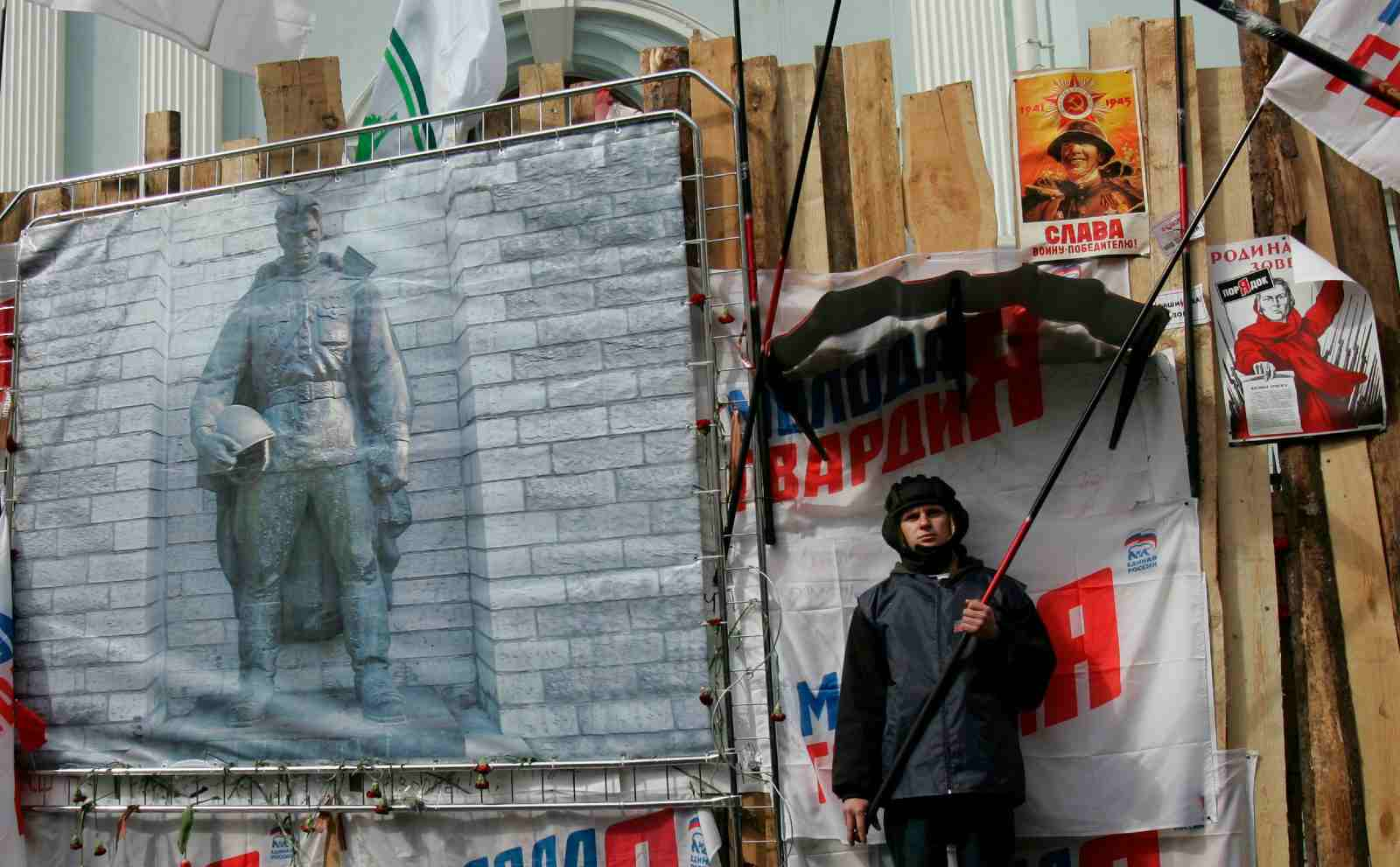 A protester holds a flag during a picket of Kremlin-loyal youth organisations in front of the Estonian embassy in Moscow May 3, 2007. The poster on the left shows the statue of a Red Army soldier, whose relocation in Tallinn has sparked recent tensions between Russian and its ex-Soviet neighbour.