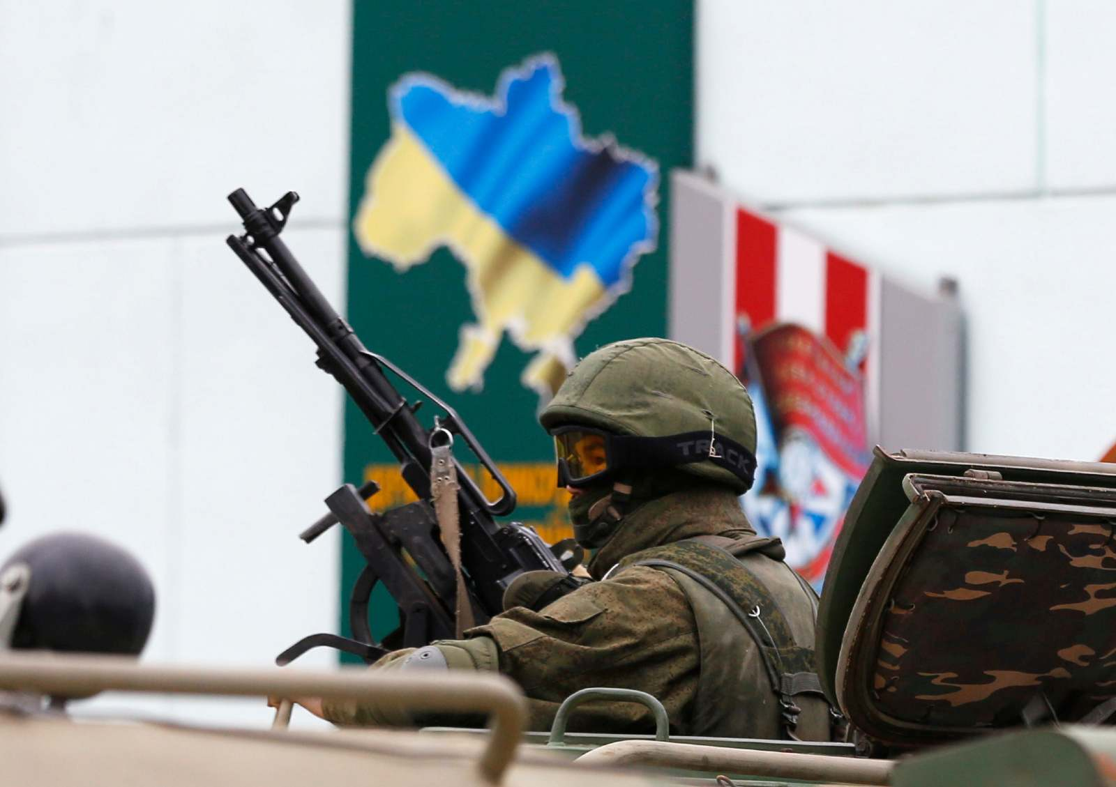 An armed serviceman looks out from a Russian army vehicle outside a Ukrainian border guard post in the Crimean town of Balaclava March 1, 2014. Ukraine accused Russia on Saturday of sending thousands of extra troops to Crimea and placed its military in the area on high alert as the Black Sea peninsula appeared to slip beyond Kiev's control.