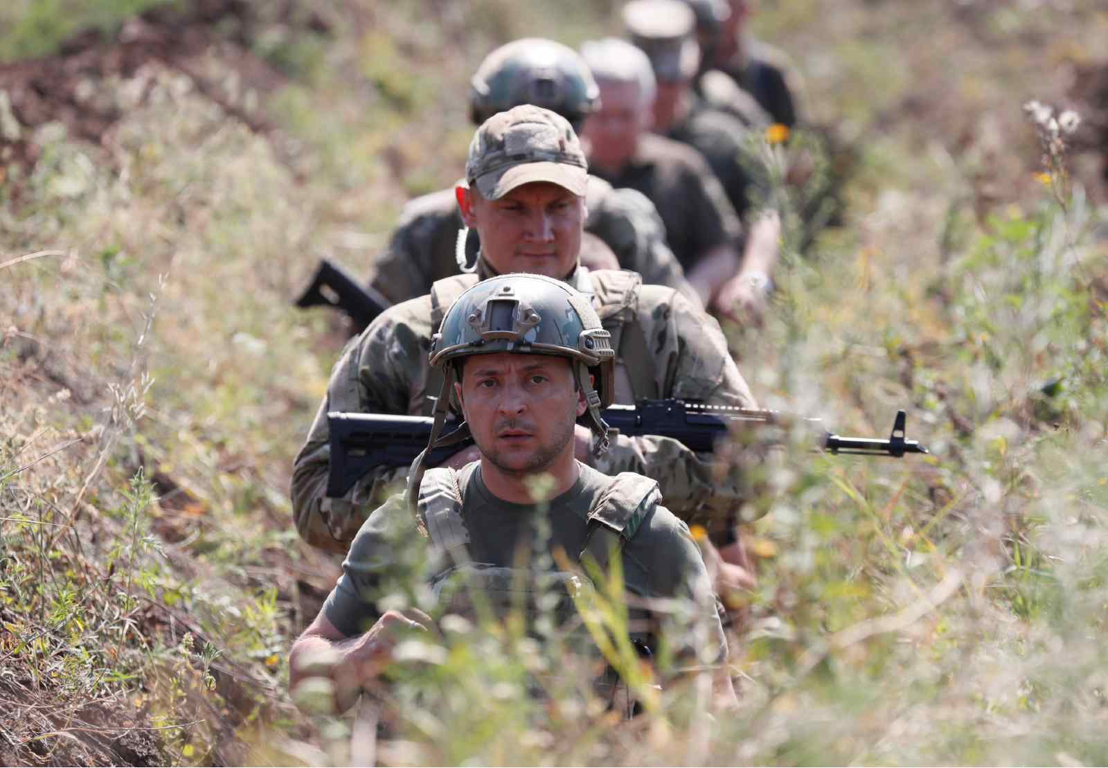 Ukraine's President Volodymyr Zelenskiy and servicemen walk in a trench near the frontline with Russian-backed separatists in Krasnohorivka in Donetsk Region, Ukraine August 7, 2020.