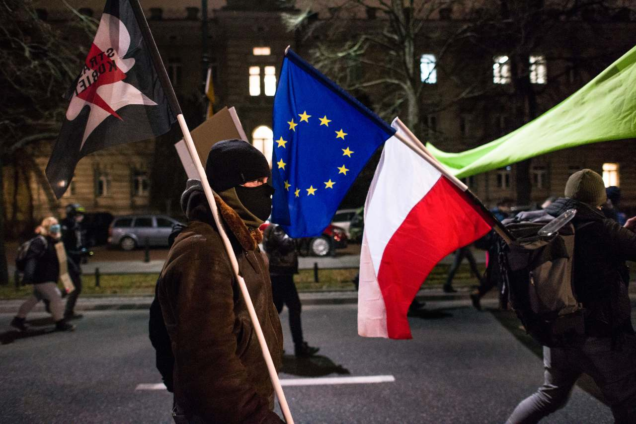 "A protester walks with the Polish and the EU flag tied together during the demonstration. Under the slogan ""A Walk for Future'' (Spacer dla Przyszlosci) hundreds of students gathered at the Chancellery demanding the resignation of Prime Minister, Przemyslaw Czarnek from the ruling Law and Justice (PiS) party as the minister of education and science, whom they described as ""a homophobic minister proclaiming controversial views."" The Women's Strike (Strajk Kobiet) and the Youth Strike for Climate (MSK) also joined the educational strike. (Photo by Attila Husejnow / SOPA Images/Sipa USA)"