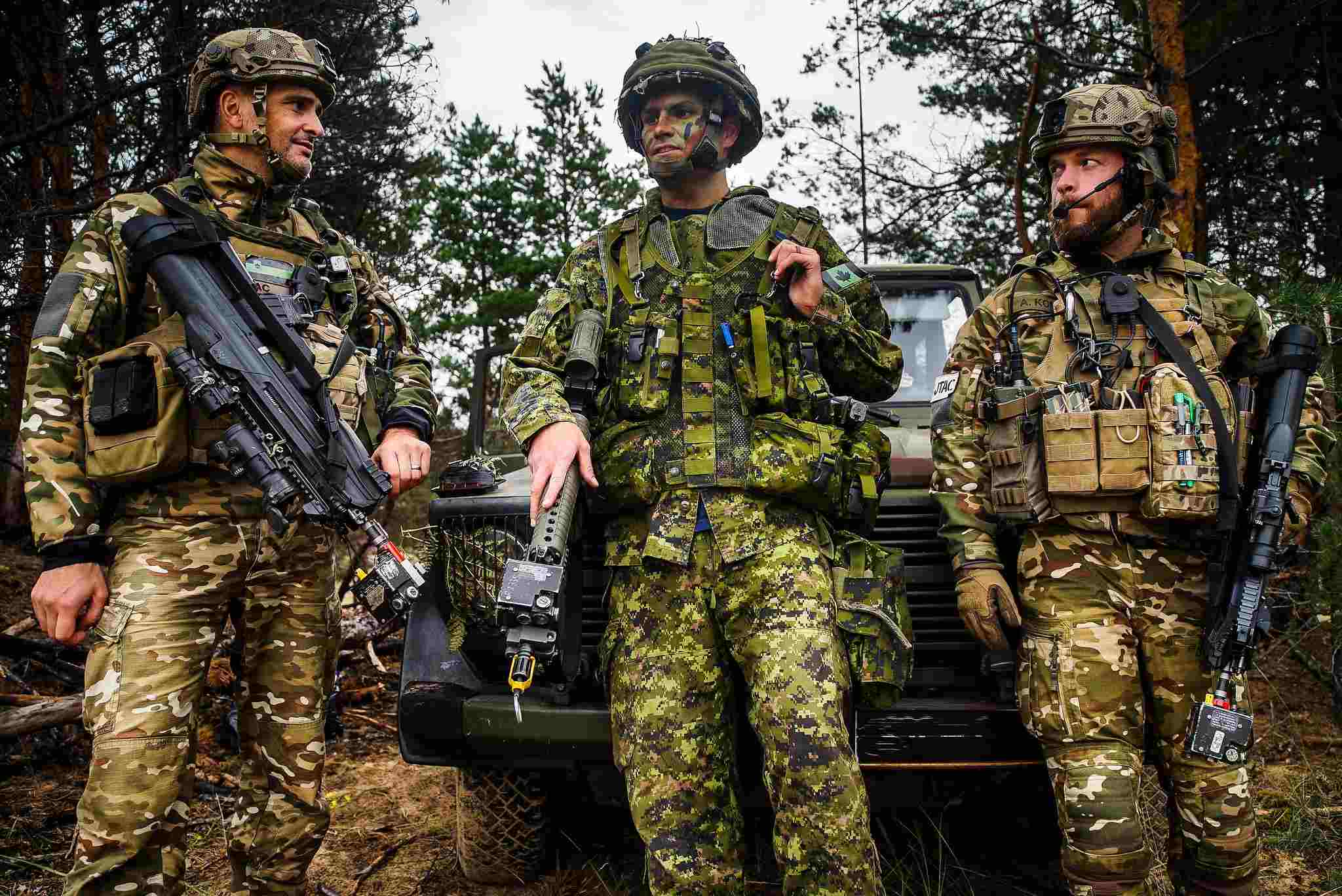 A Canadian officer from the 3rd Canadian Division speaks to members of the Slovenia J-TAC during a certification exercise. Members of the multinational battlegroup making up part of NATO's enhanced forward presence in Eastern Europe at Camp Adazi in Latvia. Credit: NATO
