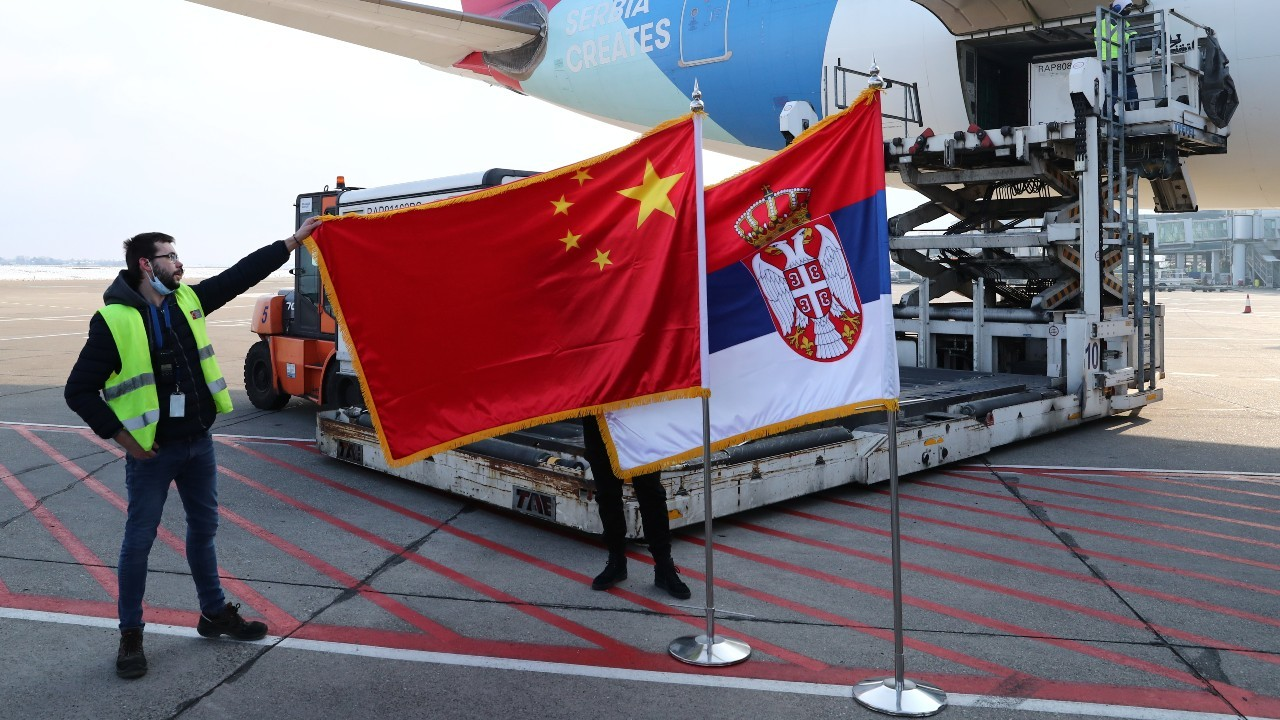 A man holds China's flag next to Serbia's flag as a plane transporting one million doses of Sinopharm's China National Biotec Group (CNBG) vaccines for the coronavirus disease (COVID-19) arrives at Nikola Tesla Airport in Belgrade, Serbia, January 16, 2021. REUTERS/Marko Djurica