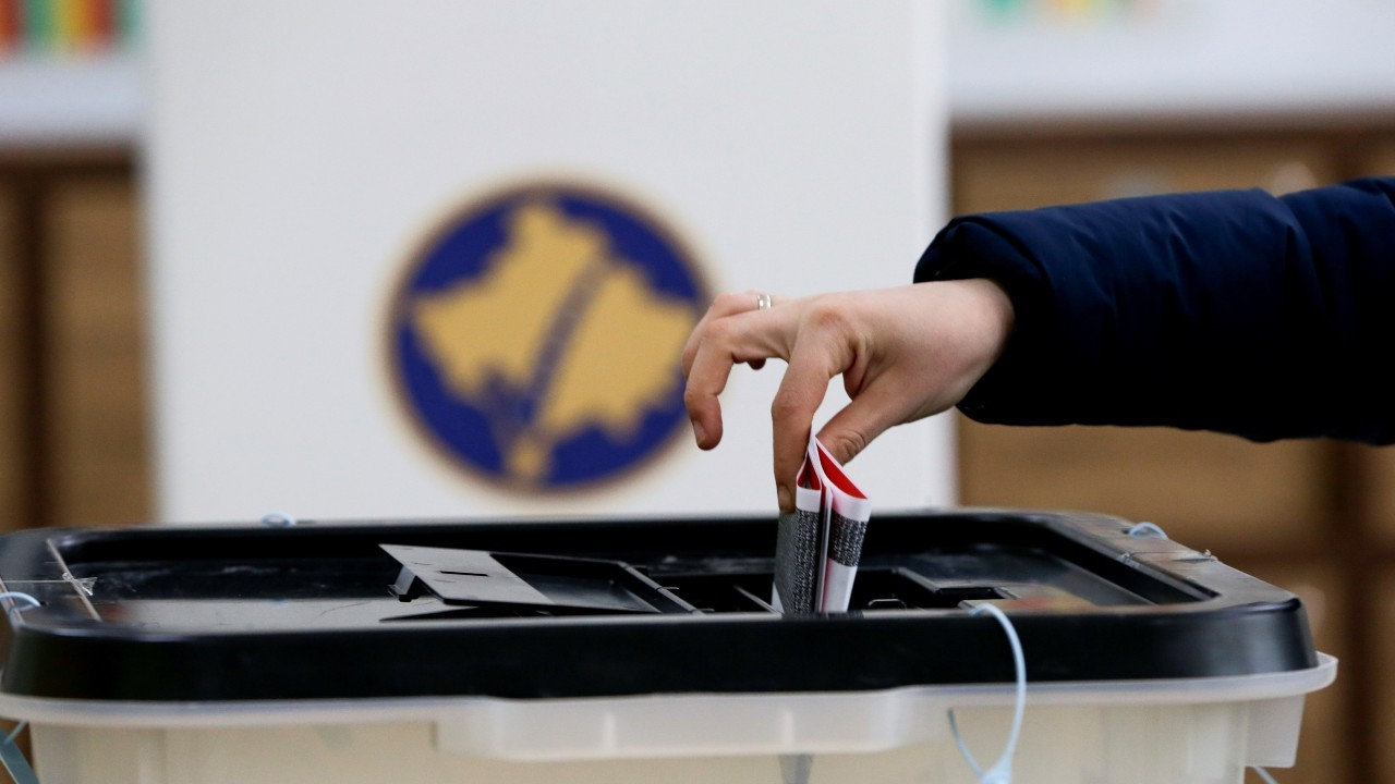 Photo: A voter casts a ballot during parliamentary elections in Pristina, Kosovo, February 14, 2021. Credit: REUTERS/Florion Goga