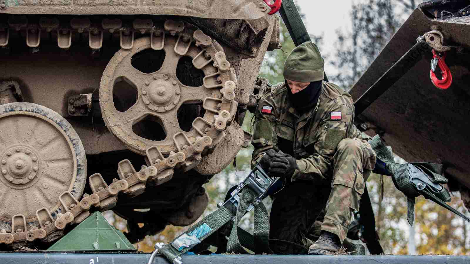 A Polish soldier walks behind armoured vehicles loaded on to rail cars during Exercise Brilliant Jump 20. Brilliant Jump is a deployment exercise designed to test the readiness of NATO's spearhead unit, the Very High Readiness Joint Task Force. The VJTF deployed to Lithuania by land, air and sea to take part in the Lithuanian national exercise Iron Wolf II. To avoid the spread COVID-19, the deploying forces avoided civilian populations on their way to Lithuania and practiced social distancing.