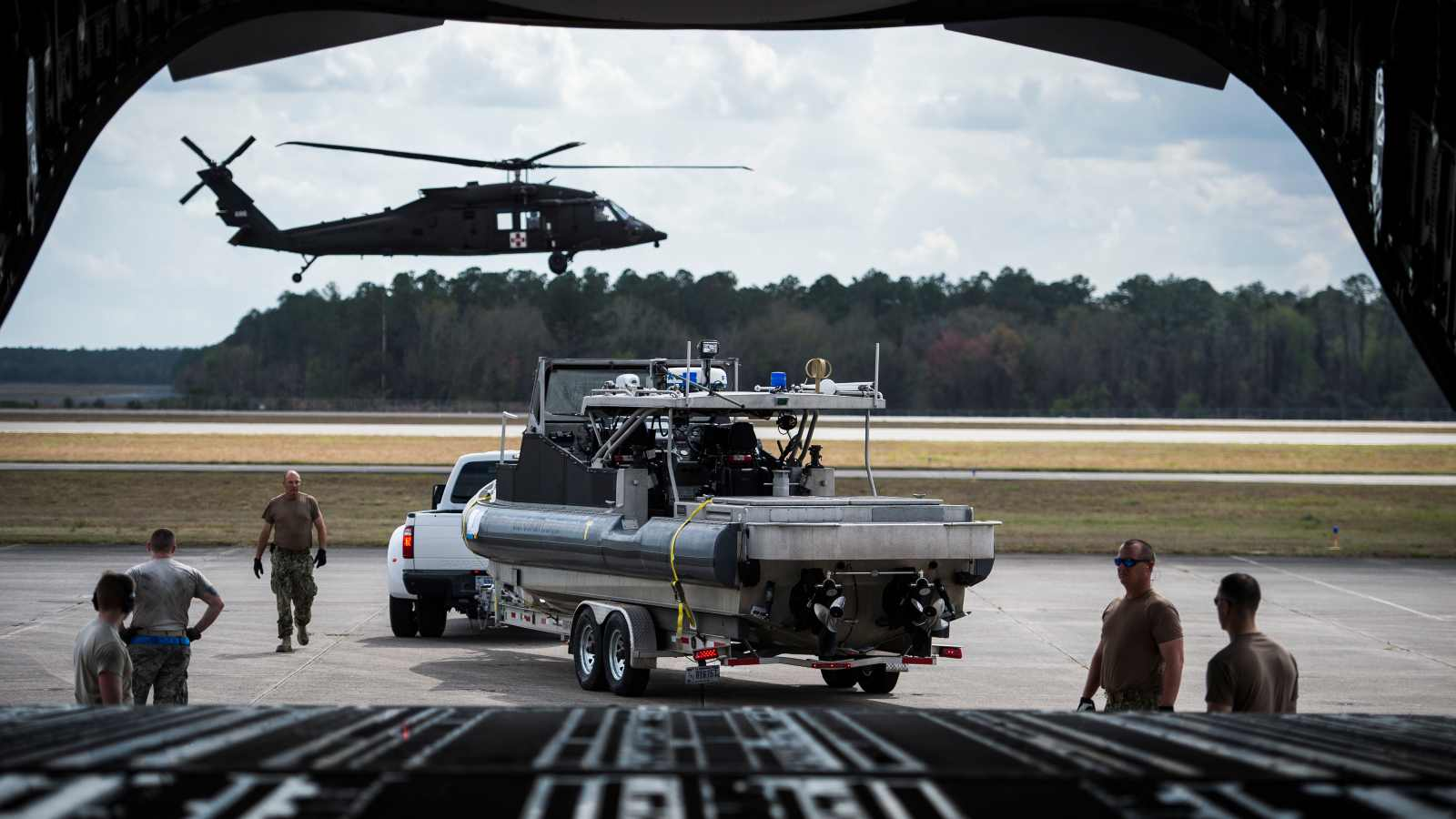 A U.S. Coast Guard boat is parked in position to be loaded onto an Air Force C-17 Globemaster, as an Army UH-60 Black Hawk prepares to land during Exercise Patriot Sands, Naval Air Station Cecil Field, Florida, Feb. 22, 2019. Exercise Patriot Sands is a joint-service exercise coordinated by the Air Force Reserve, designed to integrate first responders from federal, state, local agencies and the military by providing quick response training in the event of a regional emergency or natural disaster. (U.S. Air Force photo by Tech. Sgt. Larry E. Reid Jr.)