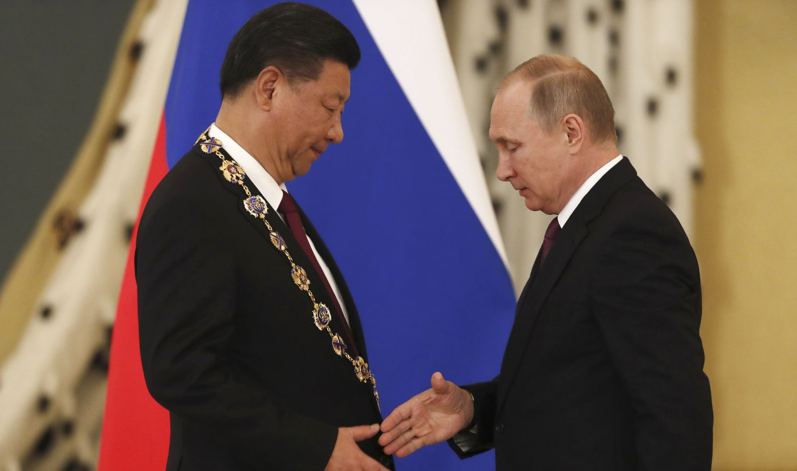 Russian President Vladimir Putin (R) shakes hands with his Chinese counterpart Xi Jinping after awarding him with the Order of St. Andrew the Apostle the First-Called during a meeting at the Kremlin in Moscow, Russia July 4, 2017. REUTERS/Sergei Ilnitsky/Pool.