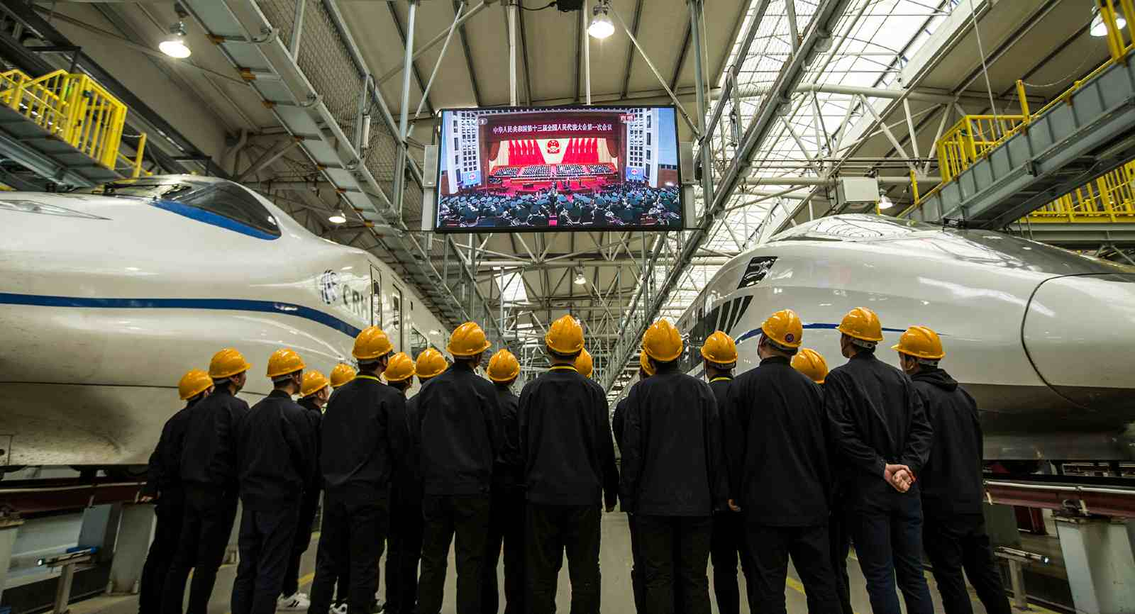 Photo: Chinese workers of CRH (China Railway High-speed) watch the live broadcast of Chinese Premier Li Keqiang delivering a government work report during the opening meeting for the First Session of the 13th National People's Congress (NPC) at a maintenance station in Xi'an city, northwest China's Shaanxi province, March 5, 2018. Credit: Oriental Image via Reuters.