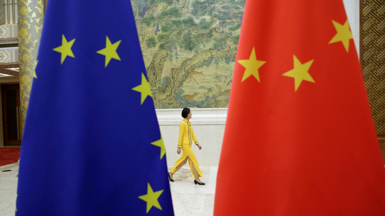 An attendant walks past flags of EU and China ahead of the EU-China High-level Economic Dialogue at Diaoyutai State Guesthouse in Beijing, China June 25, 2018. REUTERS/Jason Lee