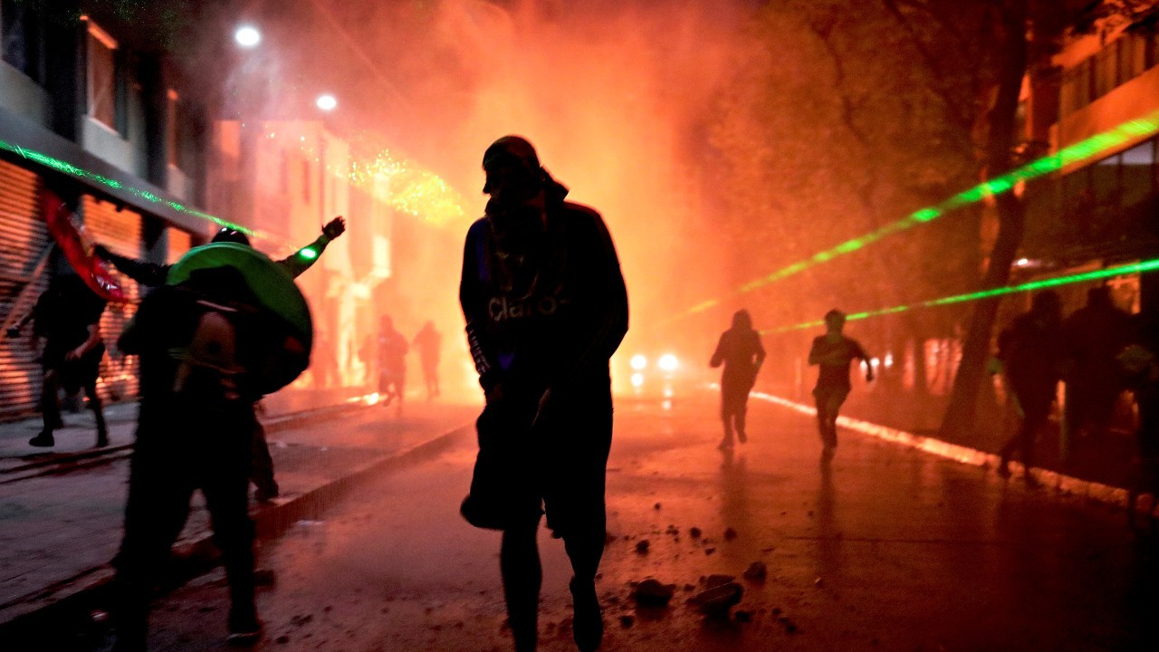 Photo: Demonstrators react on the street amid laser beams during a protest against Chile's government in Santiago, Chile December 31, 2019. Credit: REUTERS/Pablo Sanhueza