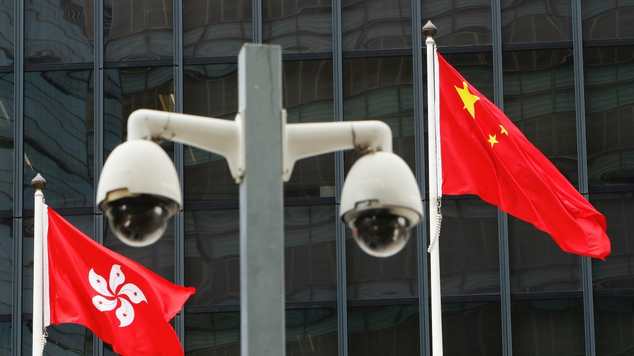 Photo: Hong Kong and Chinese national flags are flown behind a pair of surveillance cameras outside the Central Government Offices in Hong Kong, China July 20, 2020. Credit: REUTERS/Tyrone Siu