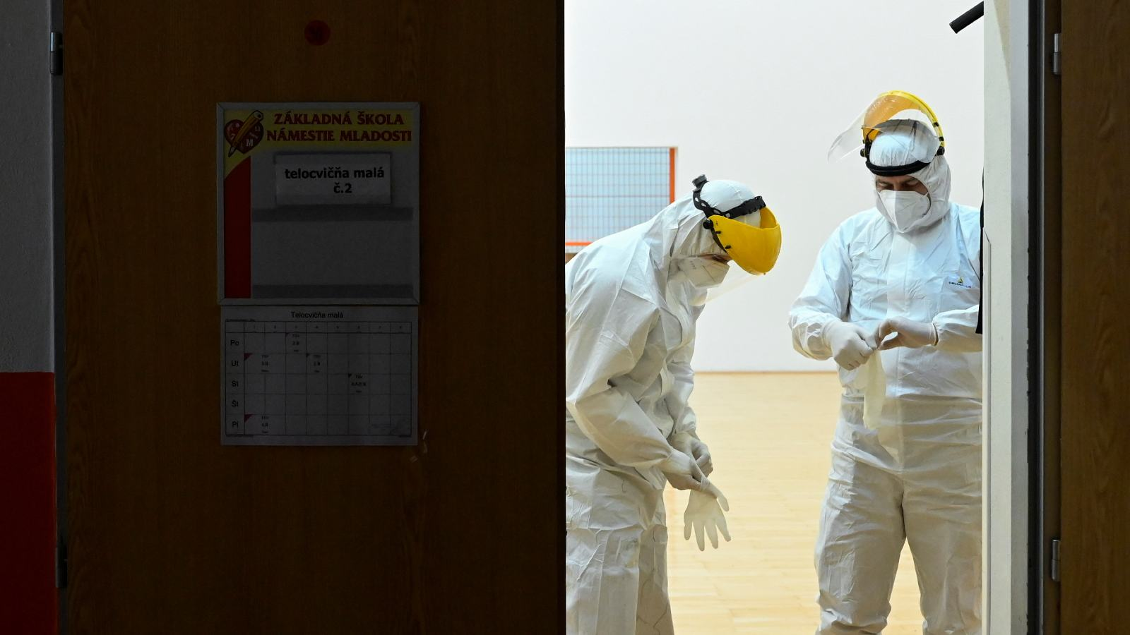 Photo: Polish healthcare workers put on their PPE during a mass nationwide testing for coronavirus disease (COVID-19) in Zilina, Slovakia, January 23, 2021. Credit: REUTERS/Radovan Stoklasa