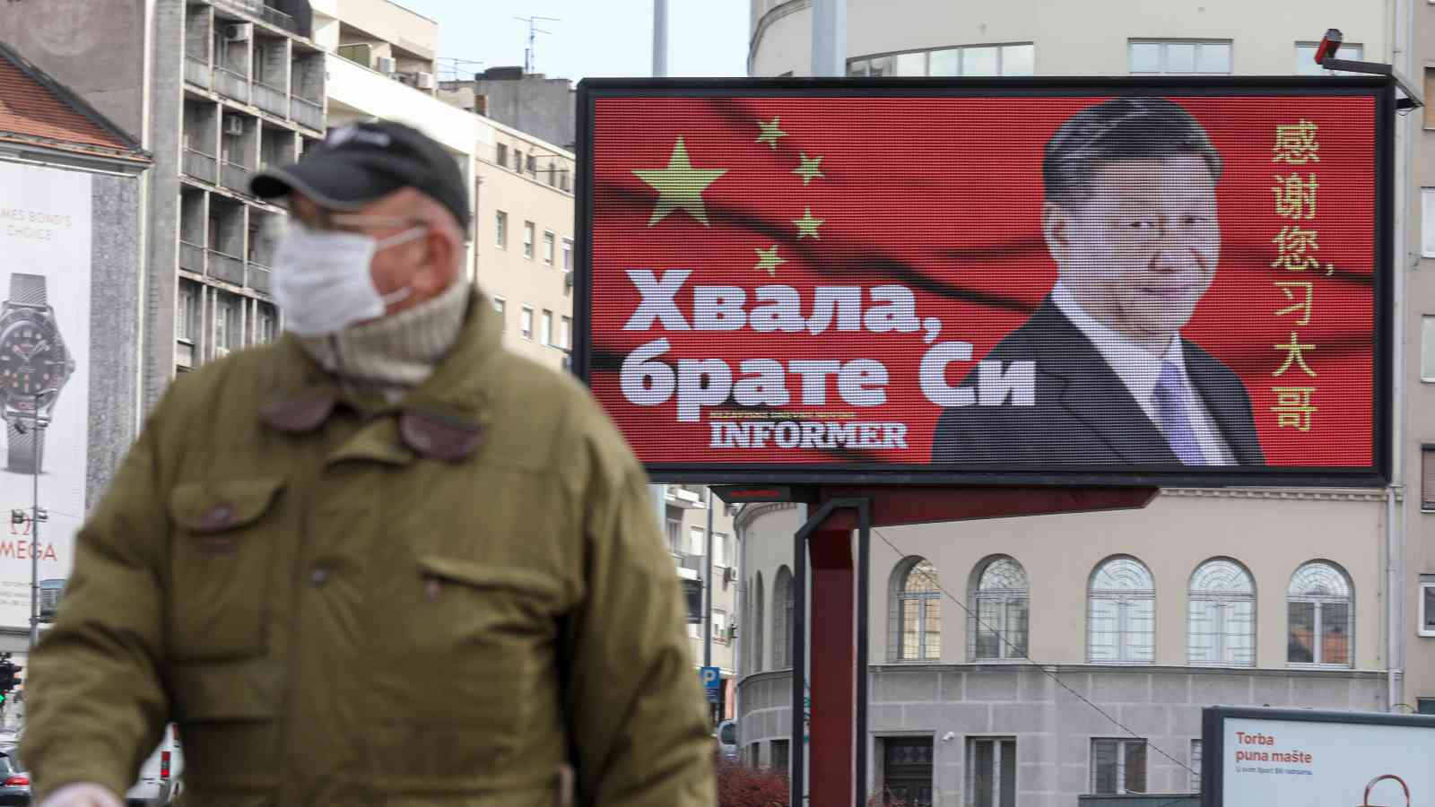 "Photo: A man wearing a protective mask passes by a billboard depicting Chinese President Xi Jinping as the spread of the coronavirus disease (COVID-19) continues in Belgrade, Serbia, April 1, 2020. The text on the billboard reads ""Thanks, brother Xi"". Picture taken April 1, 2020. Credit: REUTERS/Djordje Kojadinovic"