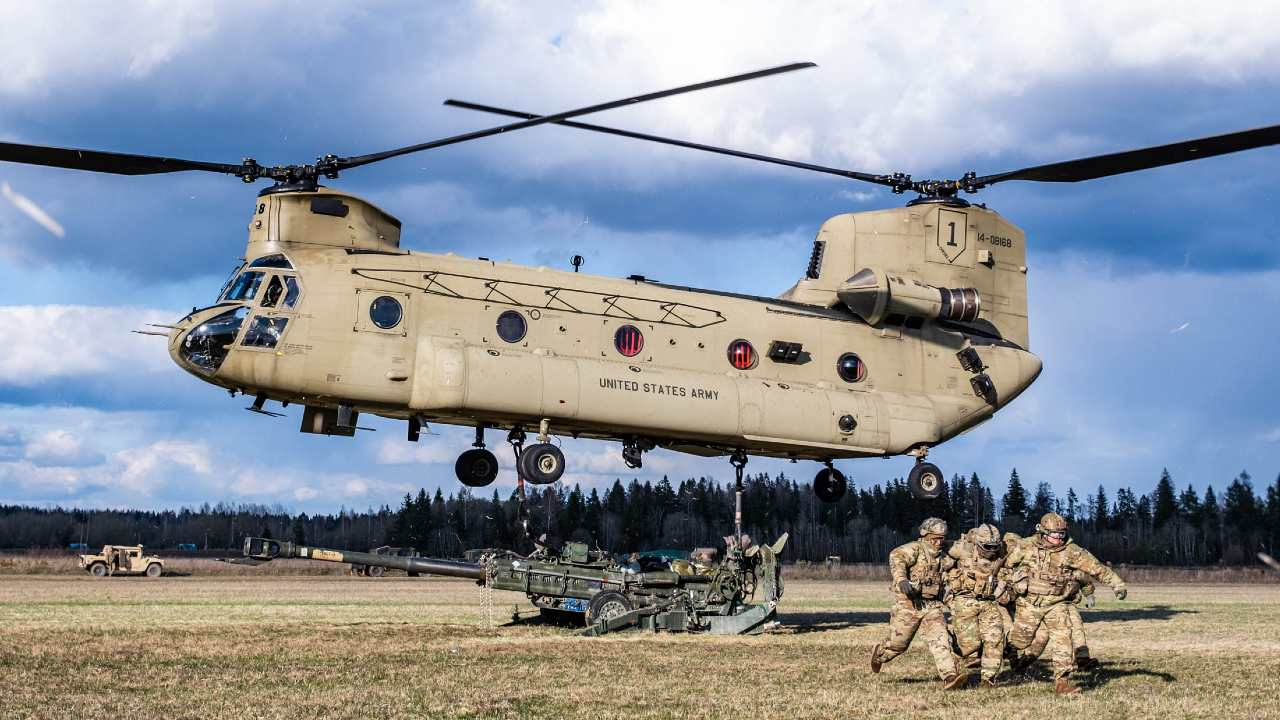Photo: US Army paratroopers from the 82nd Airborne Division clear the area so that a Chinook helicopter can lift an M-777 Howitzer during exercise Swift Response. Credit: NATO
