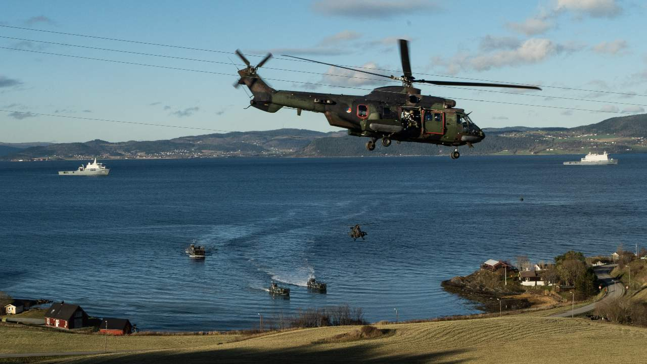 A Dutch AS532 Super Puma helicopter securises the landing of infantrymen on the beach of Trondheim Fjord, in Norway, during exercise Trident Juncture 18.