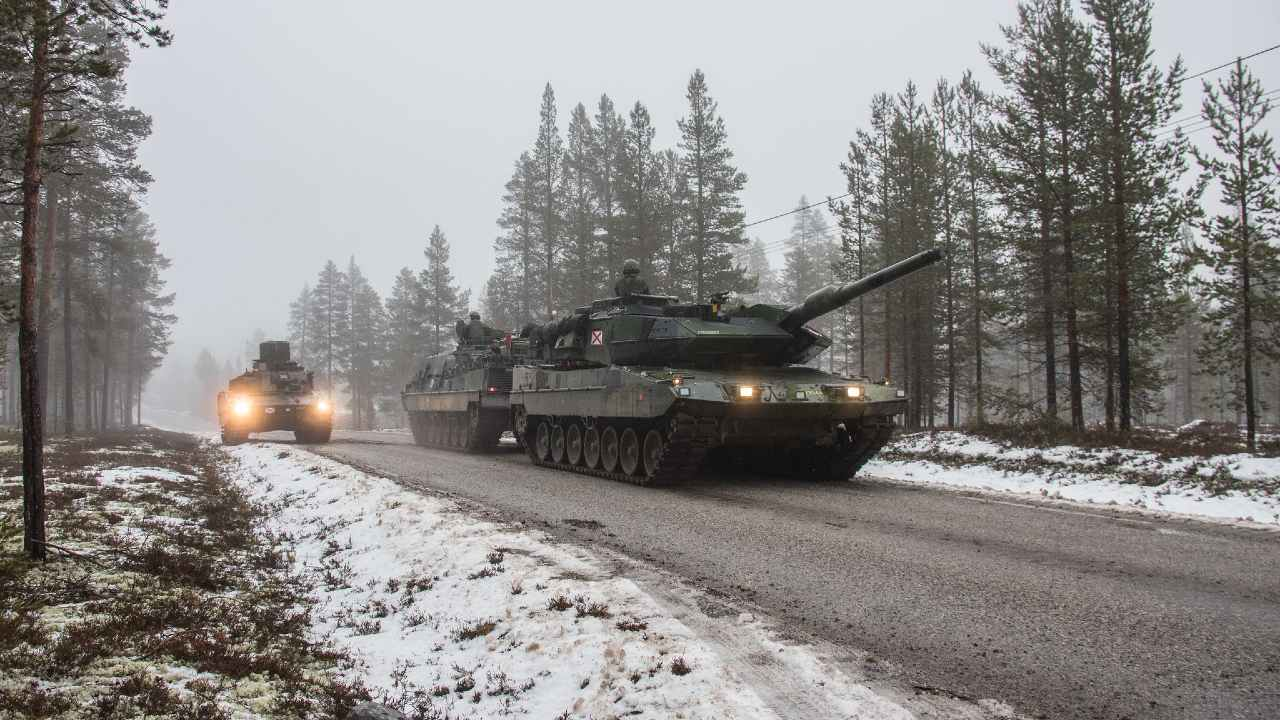 Swedish Armed Forces during Trident Juncture 2018. Swedish Leopard 122 tank taken out is towed by a tank recovery vehicle in the fog.