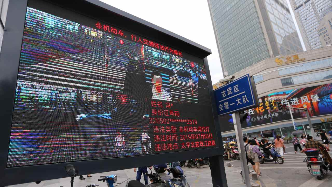 Photo: Pedestrians walk across a crossroad as a big electronic screen supported by face-recognition system shows the image of a jaywalker at the intersection in Nanjing city, east China's Jiangsu province, 4 July 2019. Traffic police in Nanjing used facial-recognition technology to capture jaywalkers in east China's Jiangsu province. Authorities already publicly name and shame people who flout the southern city's strict road rules, using CCTV cameras equipped with artificial intelligence (AI) that can recognise offenders. Credit: Wang Feng, Oriental Image