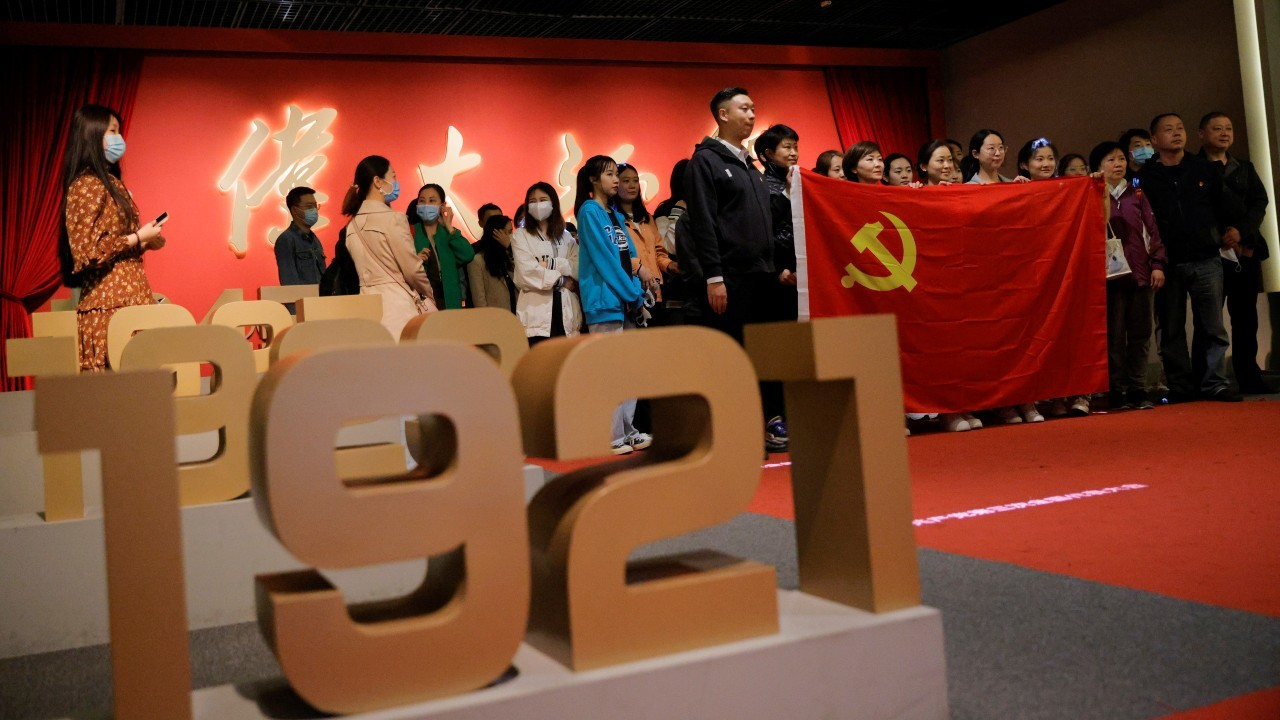 Photo: People hold the Chinese national flag as they pose for a group picture at an exhibition marking the 100th founding anniversary of the Chinese Communist Party (CCP) in Beijing, China, April 22, 2021. Credit: REUTERS/Thomas Peter