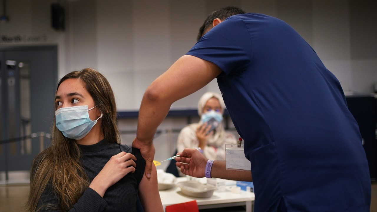 Photo: Anna Solvalag, aged 18, receives a Pfizer BioNTech COVID-19 vaccine at an NHS Vaccination Clinic at Tottenham Hotspur's stadium in north London. Sunday June 20, 2021. Credit: PA via Reuters