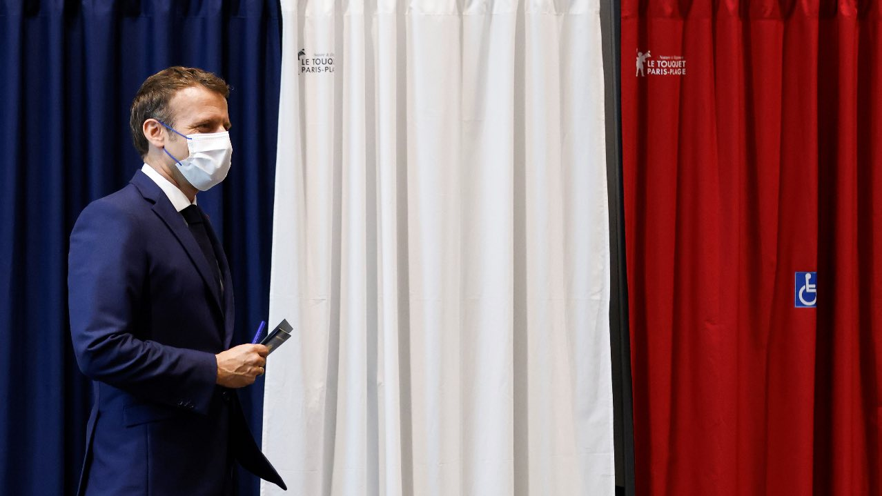 French President Emmanuel Macron leaves a booth equipped with anti-COVID curtains at a polling station in Le Touquet, France during the second round of regional elections on June 27, 2021. Ludovic Marin/Pool via REUTERS