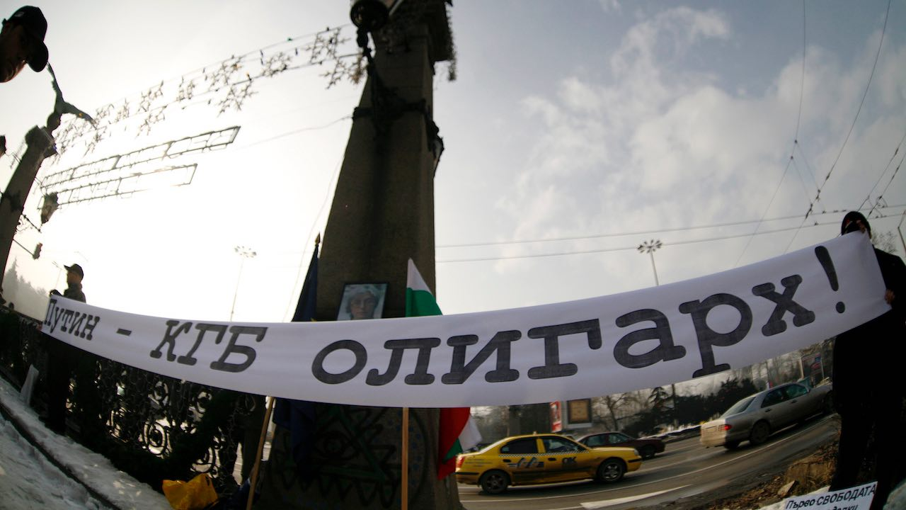 """Photo: Protestors hold a banner which reads, """"Putin - KGB oligarch"""", during a protest in Sofia, January 17, 2008. Russian President Vladimir Putin will seek closer energy ties with Bulgaria during a visit to Sofia starting on Thursday, but faces protests over the former Soviet satellite state's growing economic contacts with Moscow. Picture taken with a fisheye lens. Credit: REUTERS/Stoyan Nenov"""