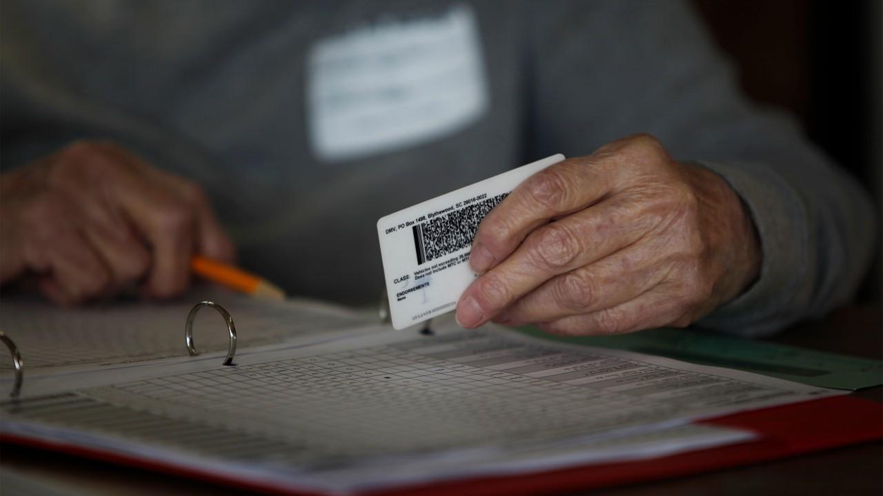 Photo: A precinct worker checks a voter ID at the Bermuda precinct for the U.S. presidential election in Dillon, South Carolina, November 8, 2016. Credit: REUTERS/Randall Hill