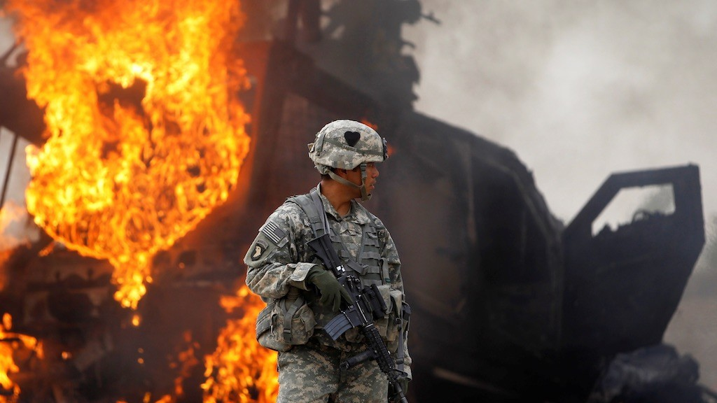 Photo: Captain Melvin Cabebe with the US Army's 1-320 Field Artillery Regiment, 101st Airborne Division stands near a burning M-ATV armored vehicle after it struck an improvised explosive device (IED) near Combat Outpost Nolen in the Arghandab Valley north of Kandahar, Afghanistan, July 23, 2010. Credit: REUTERS/Bob Strong/File Photo