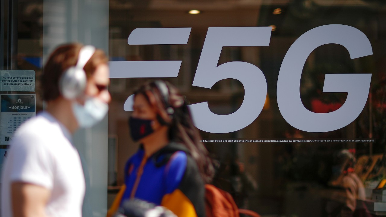Photo: People, wearing protective face masks, walk past a 5G data network sign at a mobile phone store in Paris, France, April 22, 2021. Credit: REUTERS/Gonzalo Fuentes