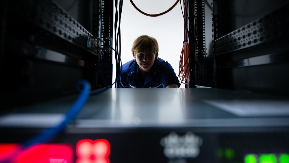 Photo: U.S. Coast Guard Chief Warrant Officer DeAnna Melleby, Information Systems Security Officer for the Coast Guard Command, Control, Communication and Information Technology unit at Coast Guard Base Boston, peers through a space in a server April 20, 2017. Melleby and her team have a number countermeasures they use to keep the Coast Guard computer network secure, including a 'sniffer' program that identifies when USBs or cell phones are plugged into the system. Credit: U.S. Coast Guard photo by Petty Officer 3rd Class Andrew Barresi