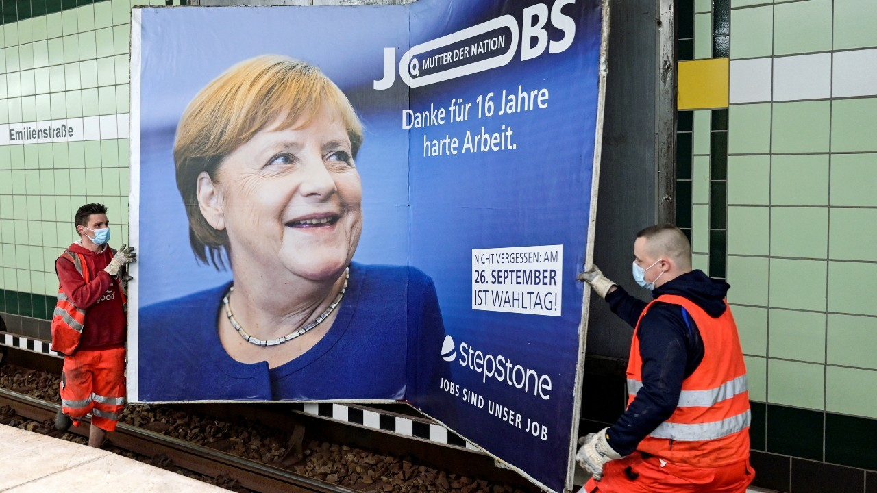 """Photo: Workers remove an advertisement showing German Chancellor Angela Merkel with a slogan that reads """"Mother of Nation - Thanks For 16 Years of Hard Work"""" before the upcoming state elections in Hamburg, Germany September 24, 2021. Credit: REUTERS/Fabian Bimmer"""