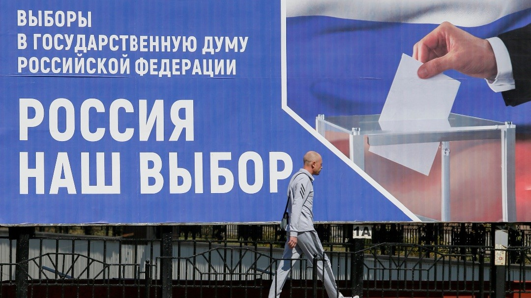 """Image:  pedestrian walks past a board informing of the upcoming Russian parliamentary elections in a street in the rebel-held city of Donetsk, Ukraine September 9, 2021. A board promotes to take part in the election by voting at polling stations in Russia's Rostov Region and reads: """"Russia is our choice"""". Credit: REUTERS/Alexander Ermochenko/File Photo"""