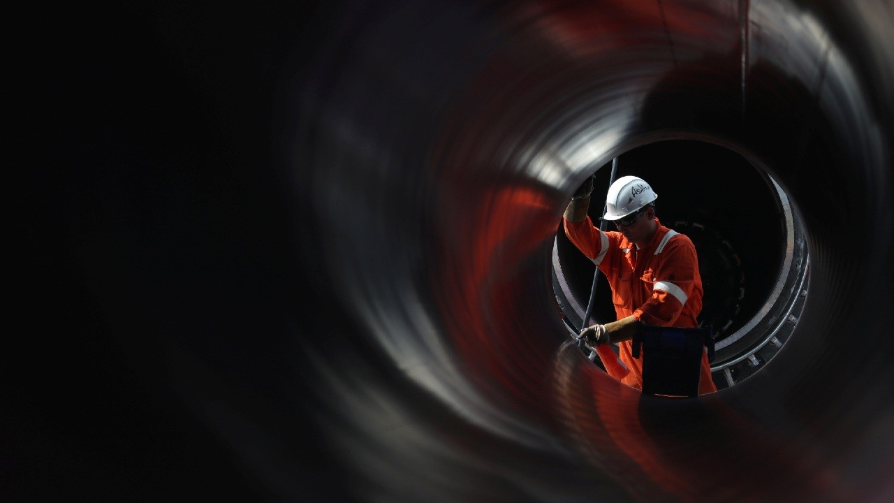 A worker is seen through a pipe at the construction site of the Nord Stream 2 gas pipeline, near the town of Kingisepp, Leningrad region, Russia, June 5, 2019. REUTERS/Anton Vaganov